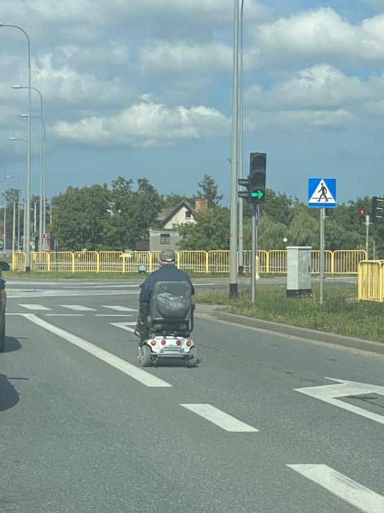 Starszy pan na wózku elektrycznym jedzie Traktem św. Wojciecha