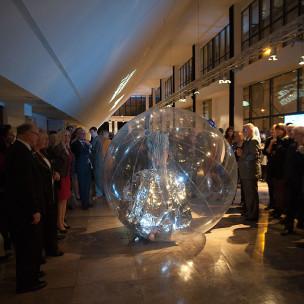 Przezroczysta kula z tancerką przetacza się przez foyer