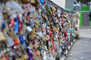 Rząd kłódek z imionami zakochanych na balustradzie Mostu Miłości w Paryżu.
