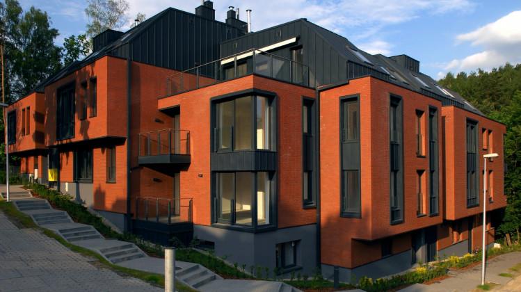 Elewacja z cegły klinkierowej i niestandardowe okna nadają budynkowi elegancji.
