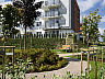 Budynki na osiedlu otoczone są zielenią i małą architekturą ogrodową.