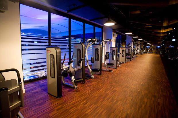 Sala fitness z widokiem na basen.