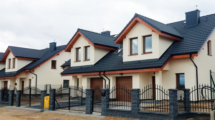 Dwukondygnacyjne domy powstają na ogrodzonych działkach.