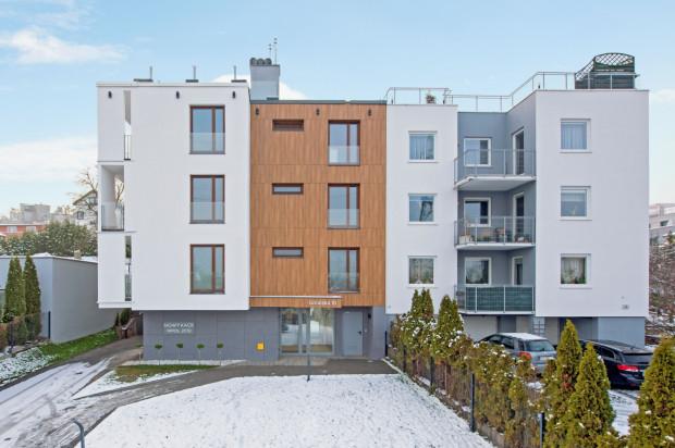 Stonowana architektura budynku komponuje się z kameralnym otoczeniem.
