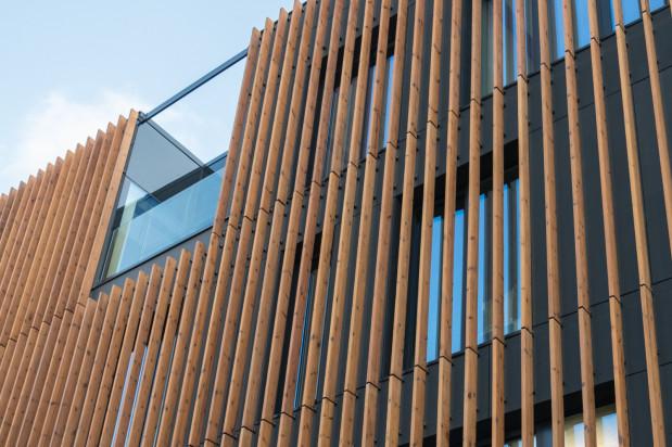 Elementy ze skandynawskiej sosny zdobią minimalistyczną elewacje budynku.