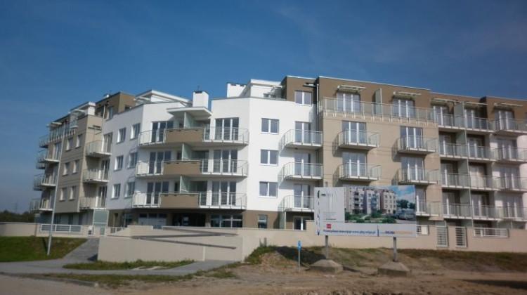 """W pierwszym budynku, w kształcie bumeranga, powstały  mieszkania z efektownymi półkolistymi balkonami nad swoistą """"bramą do osiedla"""" oraz dwa lokale usługowe."""
