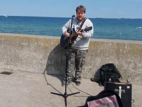Wojtek z gitarą gra na bulwarze nadmorskim w Gdyni Hallelujah po Angielsku