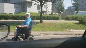 Inwalida w wózku elektrycznym jedzie ulicą