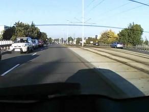Rowerzyści jadą zygzakiem między samochodami