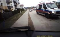 Karetka eskortująca samochód osobowy.