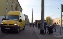 Kurier jedzie furgonetką po chodniku i...