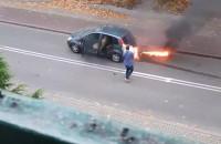 Kierowca gasi płonący samochód