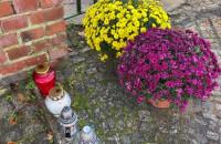 Kwiaty i znicze przed bramą cmentarza Srebrzysko