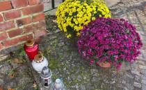 Kwiaty i znicze przed bramą cmentarza...