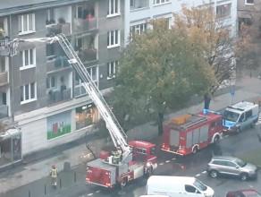 Strażacy wchodza do mieszkania oknem