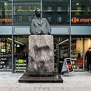 Flagi sklepu a pomiędzy nimi pomnik Kwiatkowskiego