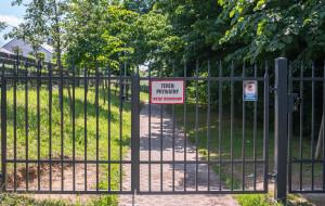 Płot i zamknięte furtki na prywatnym chodniku prowadzącym do PKM