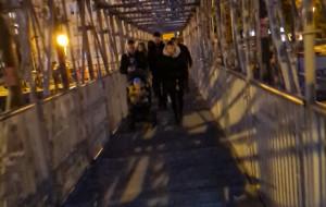 Piesi sami oświetlają przejście po tymczasowej kładce przez Motławę