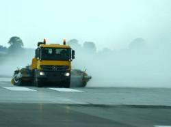 Maszyny czyszczące sprzątają pas startowy na lotnisku w Modlinie. Zalegający na nim pokruszony beton był niebezpieczny dla silników samolotów.