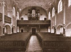 Dawne wnętrze neobarokowego kościoła. W głębi widoczne organy, które przetrwały do dziś.
