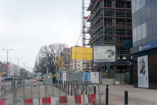 Wjazdu na budowę biurowca we Wrzeszczu pilnuje ochrona, ale - przy tak dużej budowie - ruch ciężarówek jest spory. Tuż za ogrodzeniem dźwig podnosi z ziemi kolejne elementy konstrukcji budynku.
