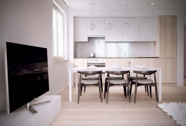 Zabudowa kuchenna z frontami z jasnego drewna, jasnym panelem szklanym w strefie międzyszafkowej, w całości ukryta we wnęce nie rzuca się w tym pomieszczeniu zbytnio w oczy.