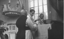 Msza św. przy jednym z ołtarzy w kościele cystersów. W tle widoczna przedwojenna ambona z ozdobnym baldachimem.