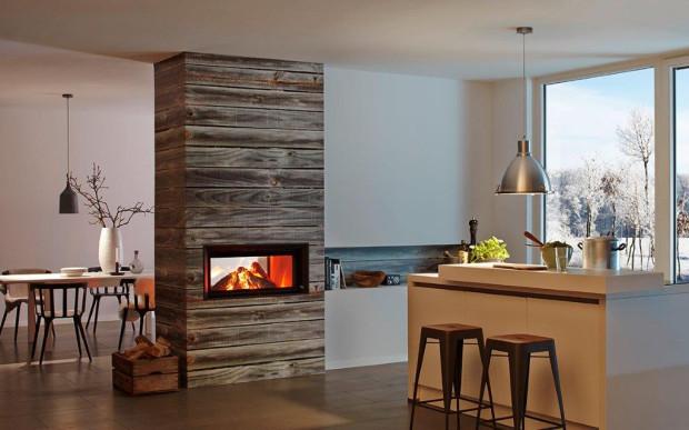 Drewniana obudowa tego kominka ociepla surowy klimat pomieszczenia.