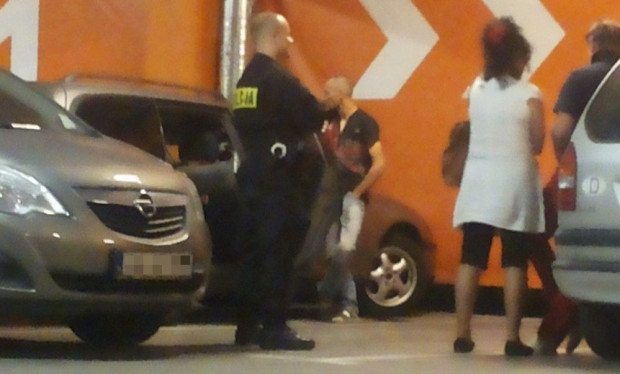 Zamknięte w samochodzie (znajdującym się w głębi zdjęcia) dzieci zauważyło starsze małżeństwo parkujące obok.