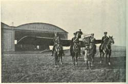 Huzarzy, samolot, a w tle fragment stacji lotniczej im. księcia Friedricha Sigismunda Hohenzollerna.