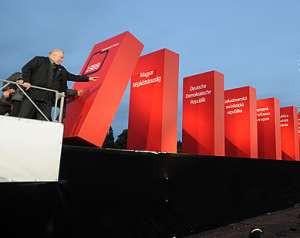 Lech Wałęsa przewraca domino symbolicznie ukazujące upadek komunizmu w krajach Europy Wschodniej.