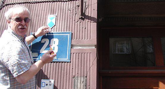 Grzegorz Wybierała przykręca tabliczkę, informującą, że kamienica przy ul. Abrahama 28 jest już zabytkiem.