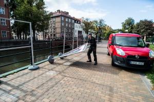 Strażnik miejski podnosi plansze przy Kanale Raduni.