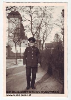 Na pierwszym planie przedwojenny policjant, na drugim nastawnia.