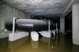 Potężne rury łączące zbiornik retencyjny z korytem Strzyży (większa rura) oraz z kanałem ulgi (mniejsza rura z tyłu). Woda widoczna na zdjęciu nie wynika z nieszczelności instalacji, a wciąż trwającej budowy i braku zabezpieczenia pięter obiektu przed wodami opadowymi.