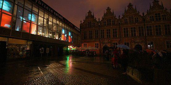 """Deszczowa pogoda nie odstraszyła widzów, którzy skupili się pod Teatrem Wybrzeże by obejrzeć i wysłuchać projektu """"Stany Złożone""""."""