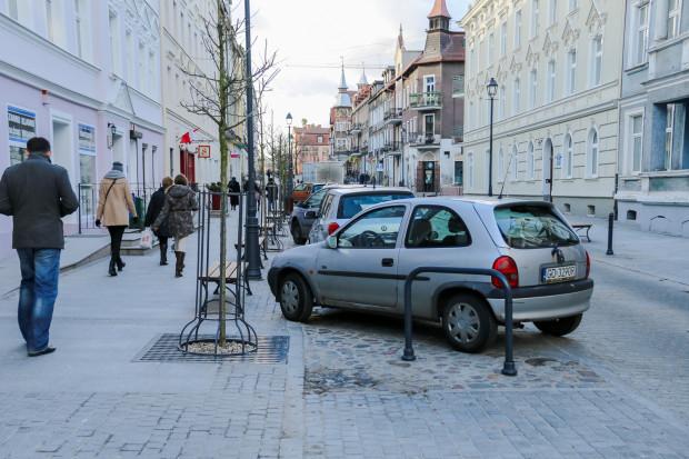 Auto parkujące skośnie w zatoce i utrudniające dostęp do stojaka rowerowego.
