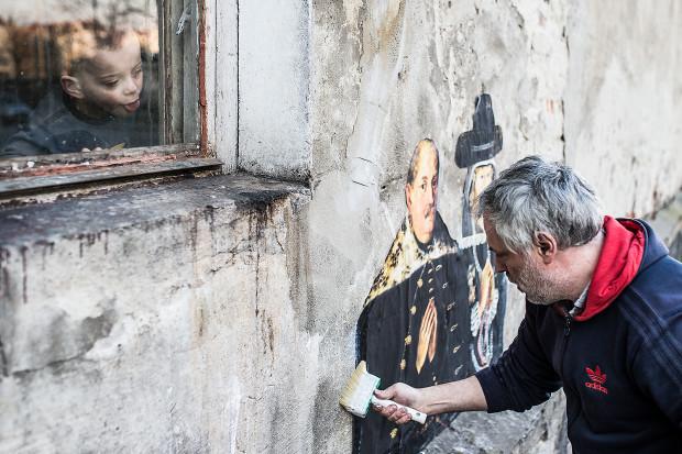 Julien de Casabianca przy pracy. Artysta nakleja fragment obrazu na murze domu na Dolnym Mieście w Gdańsku.