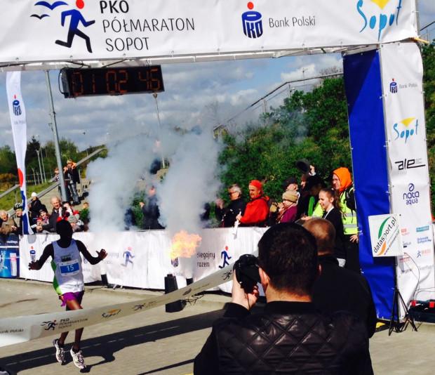 Na cześć kończących półmaraton odpalano pirotechnikę. Na zdjęciu finiszuje zwycięzca Hillary Kiptum Maiyo (Kenia).