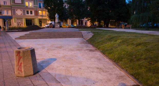 Betonowy plac od strony alei i trawa z rolki. Po prawej, w głębi skweru przeniesione ławki, zakupione przez radę dzielnicy.