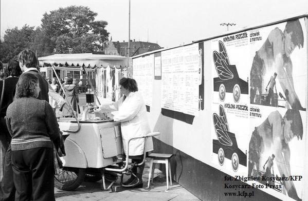 """Saturator przy budynku LOT-u. Na parkanie widać plakaty reklamujące Festiwal Polskich Filmów Fabularnych oraz """"Człowieka z marmuru"""". 1977 rok."""