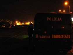 Wieczornemu mini-zlotowi z oddali przygladają się policjanci w radiowozie.
