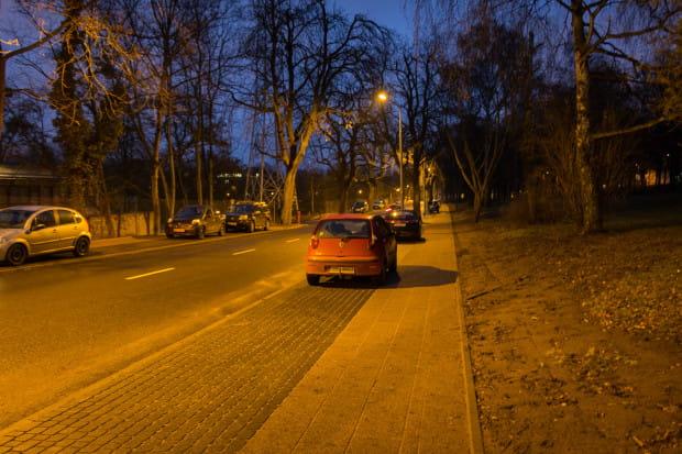 Na ul. Traugutta przestrzeń do parkowania aut wyznaczono innym materiałem, choć w miejscu bliżej PG kosztem chodnika, który ma mniej niż 1,5 m (cztery płytki po 30 cm + kilkucentymetrowy pasek).