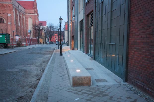 Próba dostosowania usługowego parteru budynku do okolicznych chodników na osiedlu Kwartał Kamienic.