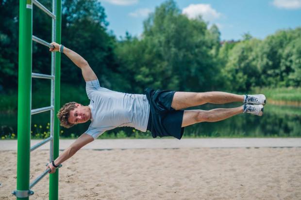 """Nie każdy trenujący kalistenikę w końcu zrobi """"flagę"""", ale jak przekonuje Grzegorz Niecko (na zdjęciu w letniej scenerii), poziom treningu można dostosować absolutnie do każdego."""