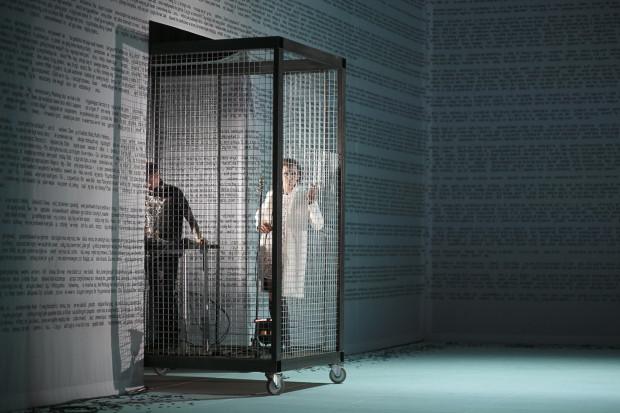 Istotną rolę w spektaklu Marcina Libera odgrywa motyw klatki. W jednej z nich, przez niemal cały czas obecnej na scenie, znajduje się Filip Kaniecki grający muzykę na żywo (po lewej) oraz Jakub Mróz w roli Kaja-narratora i wokalisty.