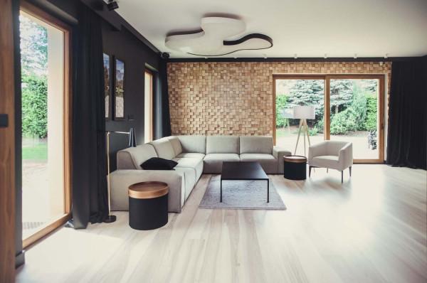 Nastrój we wnętrzu tego domu został zbudowany na zasadzie kontrastu czerni, jasnych naturalnych kolorów i drewna.