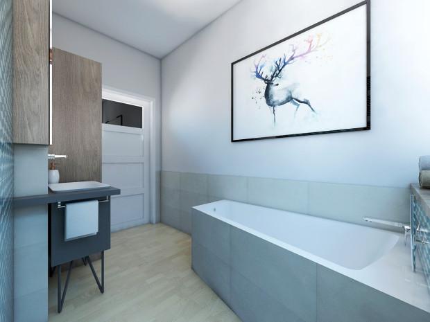 Kafle imitujące drewno na podłodze i szare kafle na obudowie wanny i ścianie stanowią przeciwwagę do intensywnych kolorów w tym wnętrzu. Efekt dopełnia grafika na ścianie.