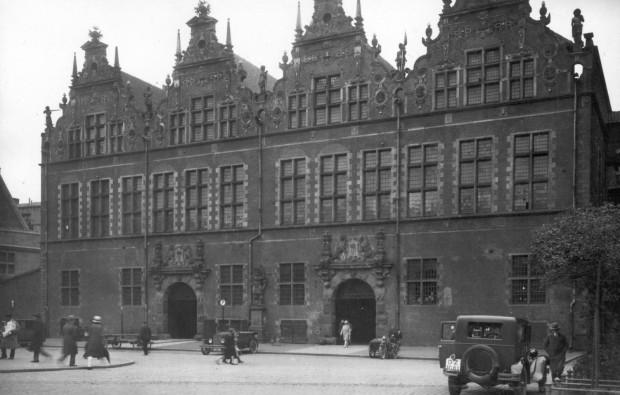 Postój taksówek przed Wielką Zbrojownią, na Targu Węglowym w Gdańsku. Zdjęcie wykonane ok. 1930 r. pochodzi z Archiwum Pomorskiego Wojewódzkiego Konserwatora Zabytków.