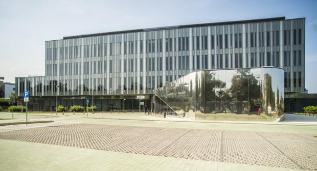 Prosta, uporządkowana w wyrazie bryła Biotechnologii kontrastuje z opływowymi fragmentami parteru. W lustrzanym wykończeniu odbija się otoczenie budynku.